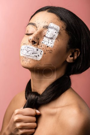 beautiful african american woman with paint splashes on face and hair around neck isolated on pink
