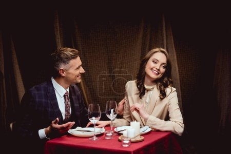 beautiful happy couple sitting at table during romantic dinner in restaurant