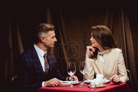 beautiful couple sitting at table and looking at each other during romantic dinner in restaurant
