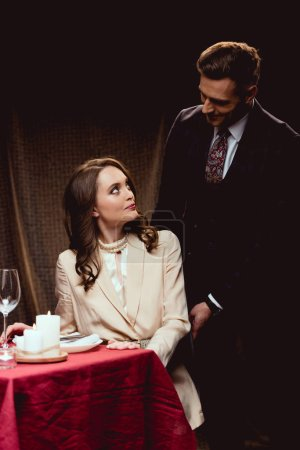 beautiful couple looking at each other during romantic dinner in restaurant