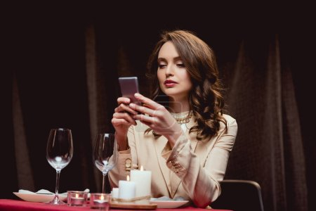 beautiful woman sitting at table and using smartphone in restaurant