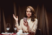 beautiful confused woman sitting at table and gesturing while using smartphone in restaurant