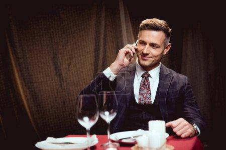 Photo pour Bel homme souriant en costume assis à table et parlant sur smartphone au restaurant - image libre de droit