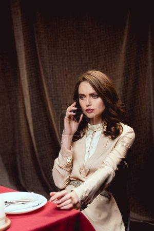 Photo pour Belle femme sérieuse assise à table et parlant sur smartphone au restaurant - image libre de droit
