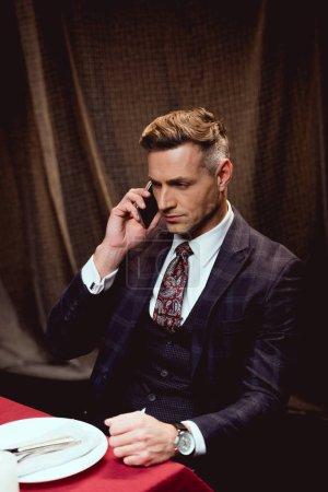 Photo pour Bel homme en costume assis à table et parlant sur smartphone dans le restaurant - image libre de droit