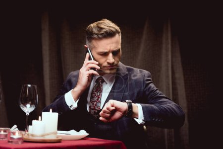 handsome man in suit sitting at table and looking at watch while talking on smartphone in restaurant