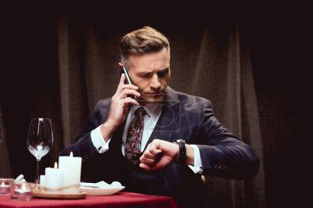 Photo pour Bel homme en costume assis à la table et regardant regarder tout en parlant sur smartphone dans le restaurant - image libre de droit