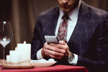 cropped view of man in suit sitting at table and using smartphone in restaurant