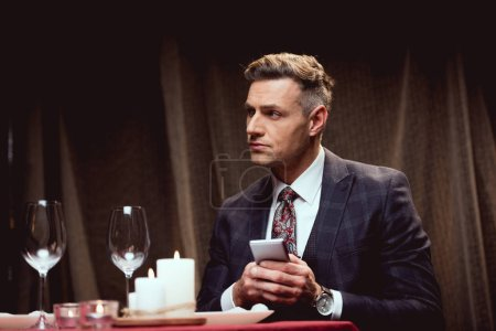 Photo pour Bel homme en costume assis à table et en utilisant smartphone dans le restaurant - image libre de droit