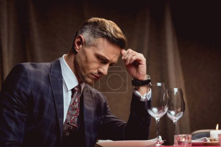 handsome pensive man sitting at table and waiting for someone in restaurant