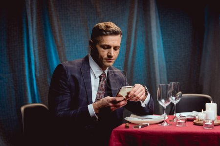 handsome man in suit sitting at table and using smartphone in restaurant