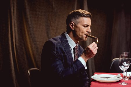 handsome man in suit sitting at table and lighting up cigar in restaurant