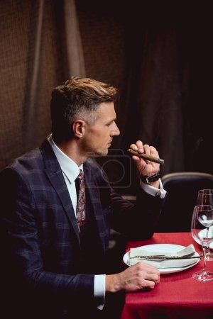 handsome man in formal wear smoking cigar in restaurant
