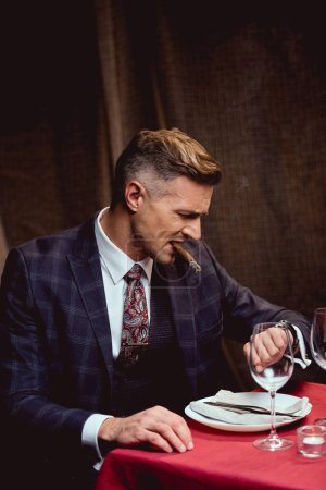 dissatisfied handsome man in suit sitting at table, smoking cigar and looking at watch in restaurant