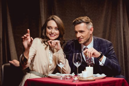 Foto de Hermosa pareja feliz sentado en la mesa y hablando durante la cena romántica en restaurante - Imagen libre de derechos