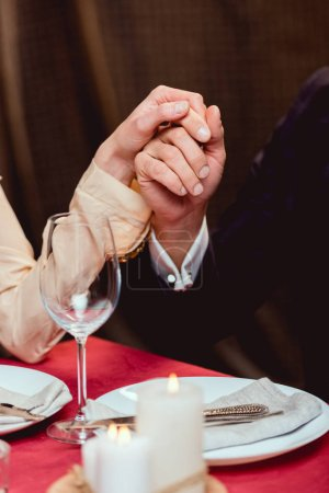 cropped view of couple holding hands during romantic date in restaurant