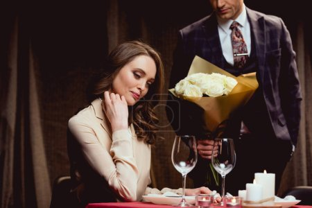 man presenting flowers to woman during romantic date in restaurant
