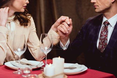 Photo pour Recadrée vue du couple main dans la main au cours de rendez-vous romantique au restaurant - image libre de droit