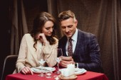 couple sitting at table and using smartphone during romantic date in restaurant