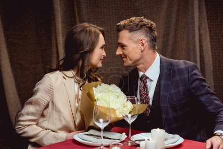 Photo for Beautiful couple sitting at table with flower bouquet and looking at each other during romantic date in restaurant - Royalty Free Image