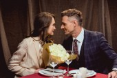 beautiful couple sitting at table with flower bouquet and looking at each other during romantic date in restaurant