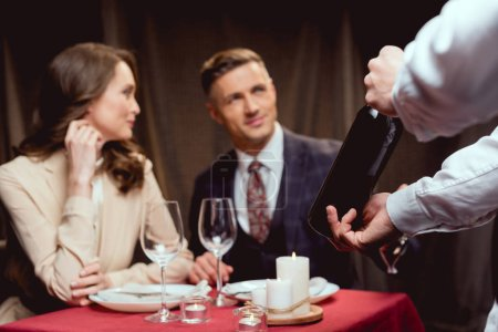 selective focus of waiter showing bottle of wine to beautiful couple during romantic date in restaurant