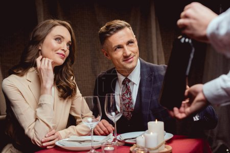 waiter showing bottle of wine to beautiful couple during romantic date in restaurant