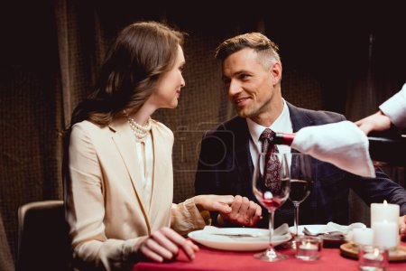 Photo for Waiter pouring red wine while couple having romantic date in restaurant - Royalty Free Image