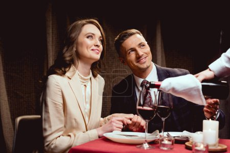Photo for Waiter pouring red wine while smiling couple having romantic date in restaurant - Royalty Free Image