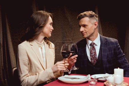 Paar sitzt am Tisch und klimpert beim romantischen Date im Restaurant mit einem Glas Rotwein