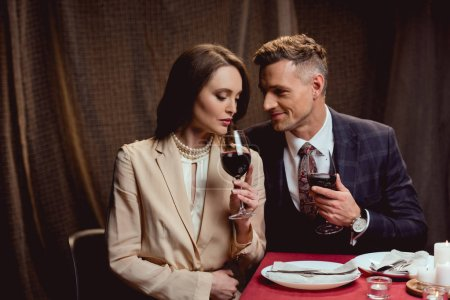 Photo for Beautiful couple holding glasses of red wine during romantic date in restaurant - Royalty Free Image