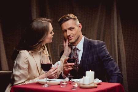 woman touching face of handsome man during romantic date in restaurant