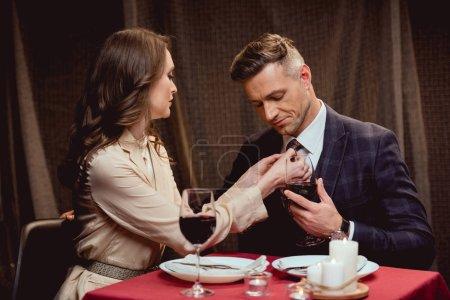 woman adjusting tie of handsome man during romantic date in restaurant