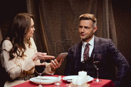 Photo for Woman holding smartphone and arguing with dissatisfied man during romantic date in restaurant - Royalty Free Image