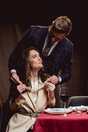 cropped view of man putting pearl necklace on woman during romantic date in restaurant