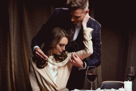 man putting pearl necklace on beautiful woman during romantic date in restaurant