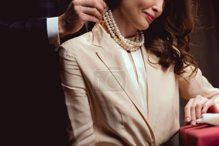 cropped view of man putting pearl necklace on smiling woman