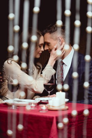 Photo for Woman gently touching face of man during romantic date in restaurant - Royalty Free Image