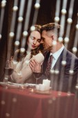 man gently embracing woman during romantic date in restaurant with bokeh lights on foreground
