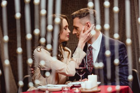 Photo for Woman gently touching face of man during romantic date in restaurant with bokeh lights on foreground - Royalty Free Image