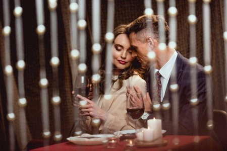 Photo for Man gently embracing woman during romantic date in restaurant with bokeh lights on foreground - Royalty Free Image