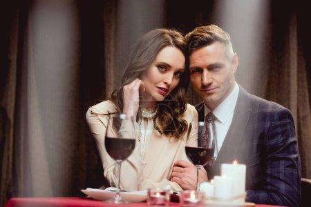 Foto de Enfoque selectivo de hermosa pareja con vasos de vino tinto mirando a cámara durante cita romántica en el restaurante - Imagen libre de derechos