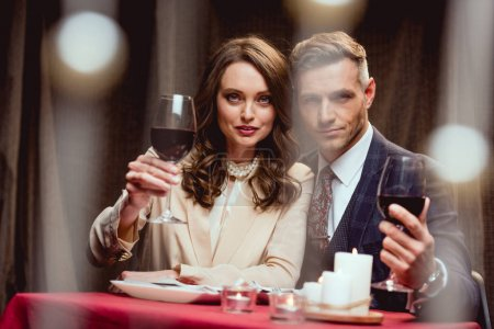 beautiful couple holding glasses of red wine and looking at camera during romantic date in restaurant