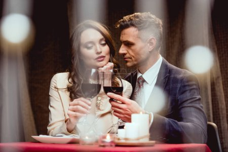 Photo for Couple clinking glasses of red wine during romantic date in restaurant with bokeh lights on foreground - Royalty Free Image