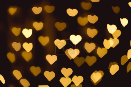 Photo for Yellow heart shaped bokeh lights on black backdrop - Royalty Free Image