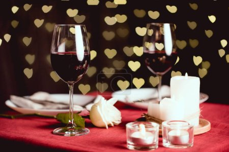 selective focus of red wine glasses with heart shaped bokeh and table setting on background