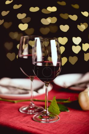selective focus of red wine glasses with heart shaped bokeh on background