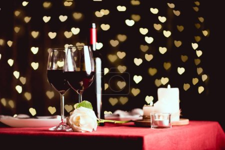 table setting with glasses of red wine, rose and heart shaped bokeh on background
