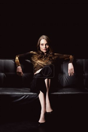 beautiful glamorous woman looking at camera while sitting on couch isolated on black