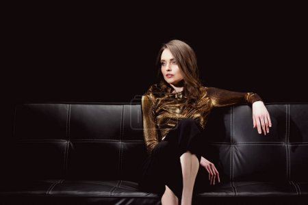 beautiful glamorous woman sitting on couch and looking away isolated on black